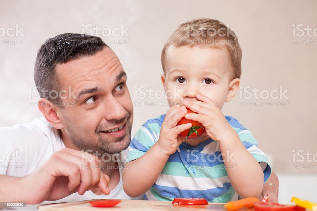 Handsome young father is feeding his kid stock photo