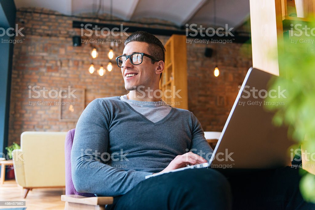 Handsome young freelancer using notebook computer for start-up business stock photo