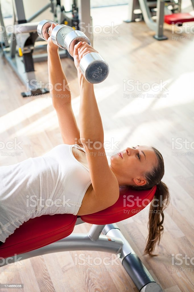 Handsome young girl rising weights royalty-free stock photo