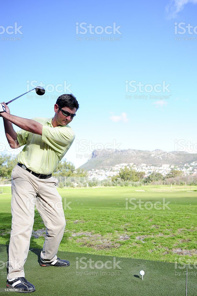 Handsome young golfer in action royalty-free stock photo