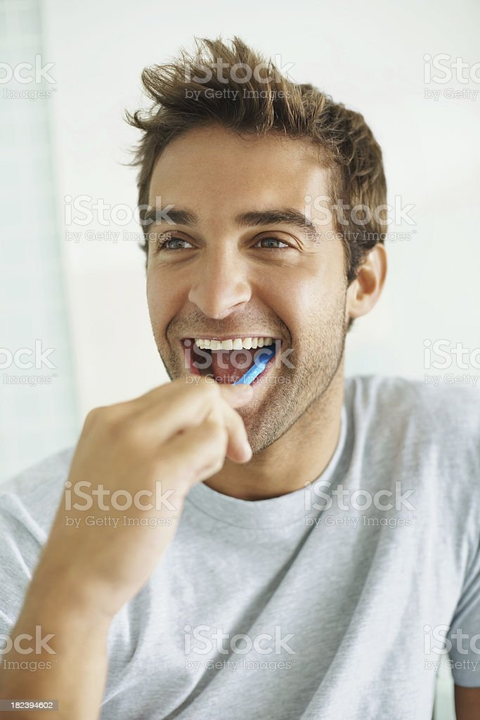 Handsome young guy brushing his teeth royalty-free stock photo