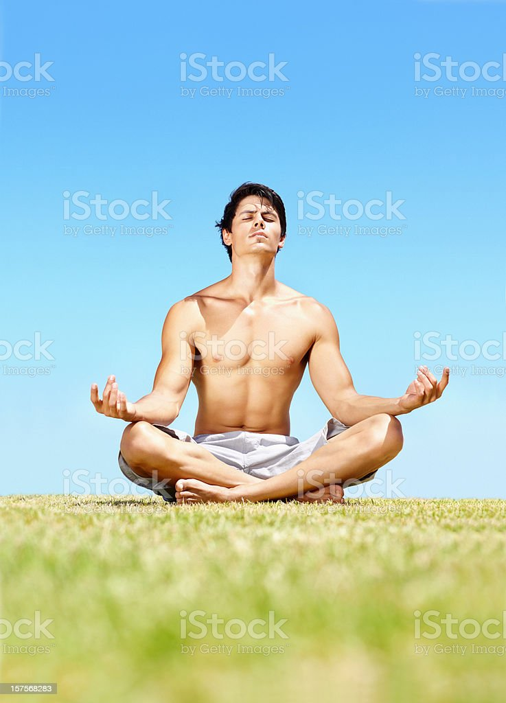 Handsome young guy meditating on a sunny day royalty-free stock photo