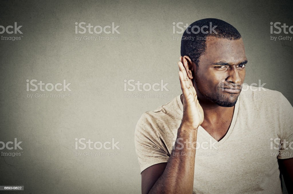 handsome young guy trying to secretly listen in on a conversation stock photo