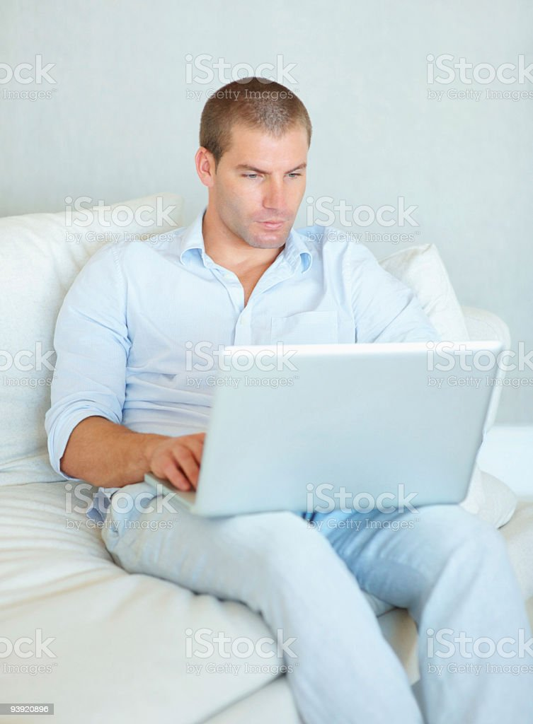 Handsome young guy using laptop at home royalty-free stock photo