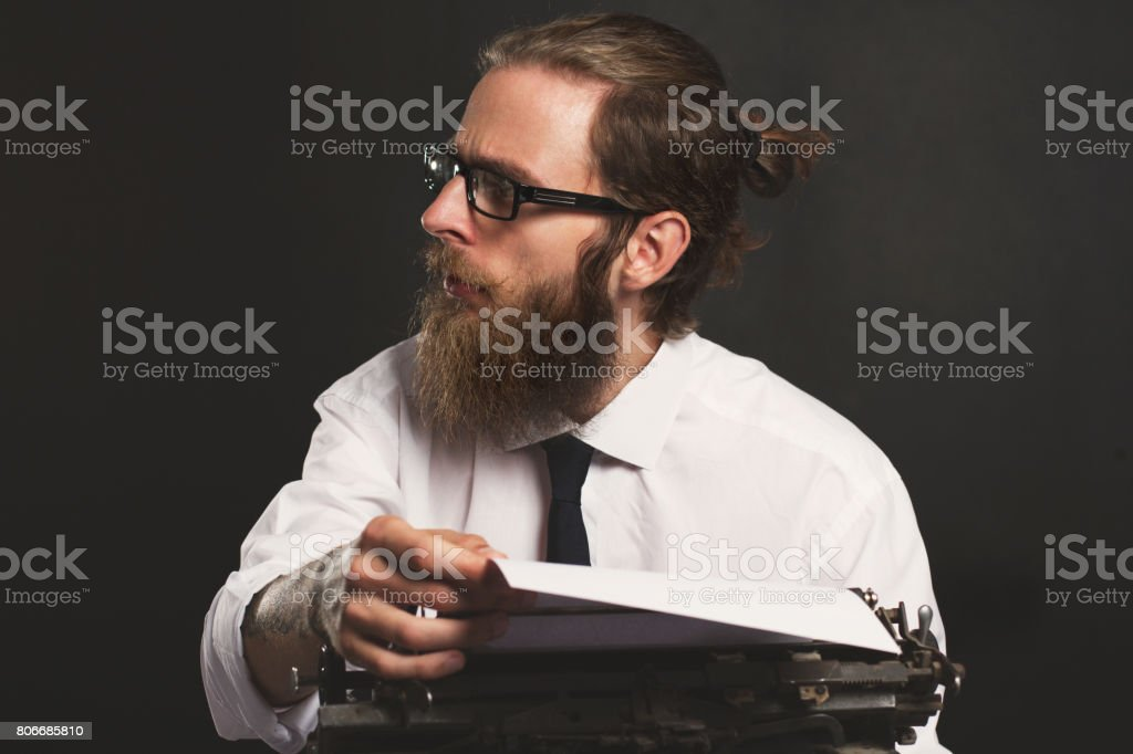 Handsome young hipster businessman thinking and writing with vintage typewriter. Old fashion style. stock photo