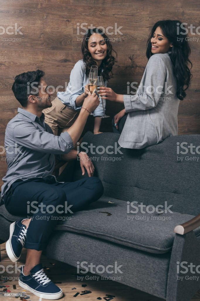 Handsome young man and smiling women toasting with glasses of champagne stock photo