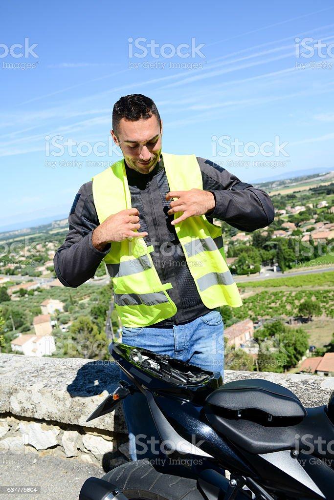 handsome young man biker yellow mandatory safety vest seat motorbike stock photo