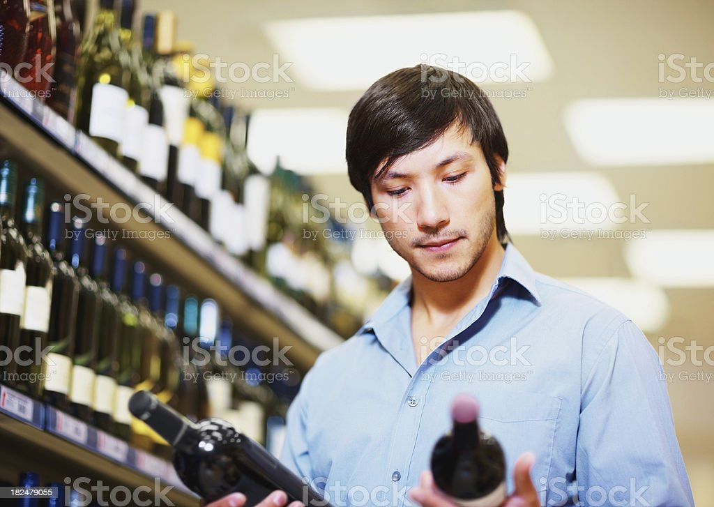 Handsome young man checking wine bottles royalty-free stock photo
