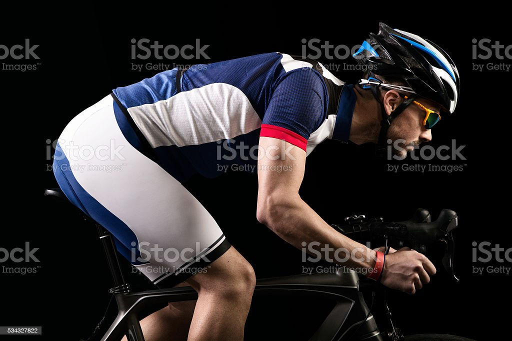 Handsome young man cycling indoor. Isolated on black. stock photo