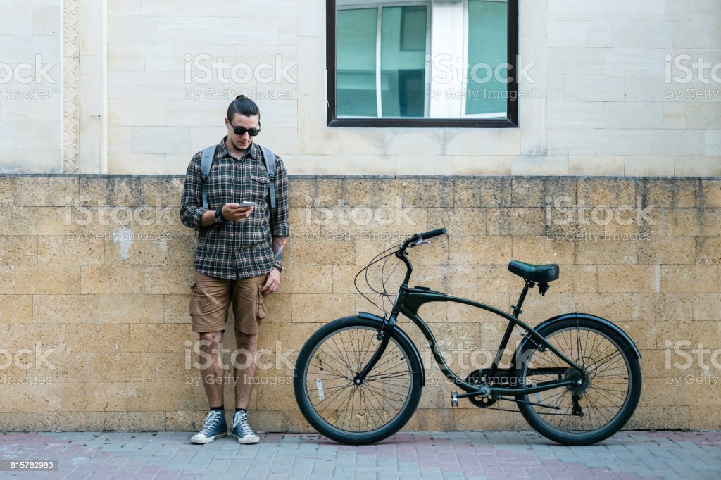 Handsome Young Man Cyclist Standing Next To Bike And His Looking At Smartphone. Street Lifestyle Urban Everyday Concept stock photo