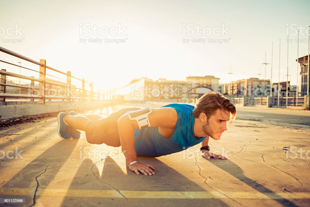 handsome young man doing push ups stock photo