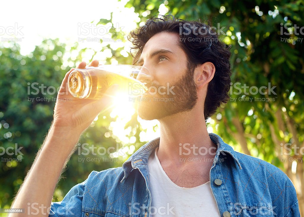 Handsome young man drinking beer in summer stock photo