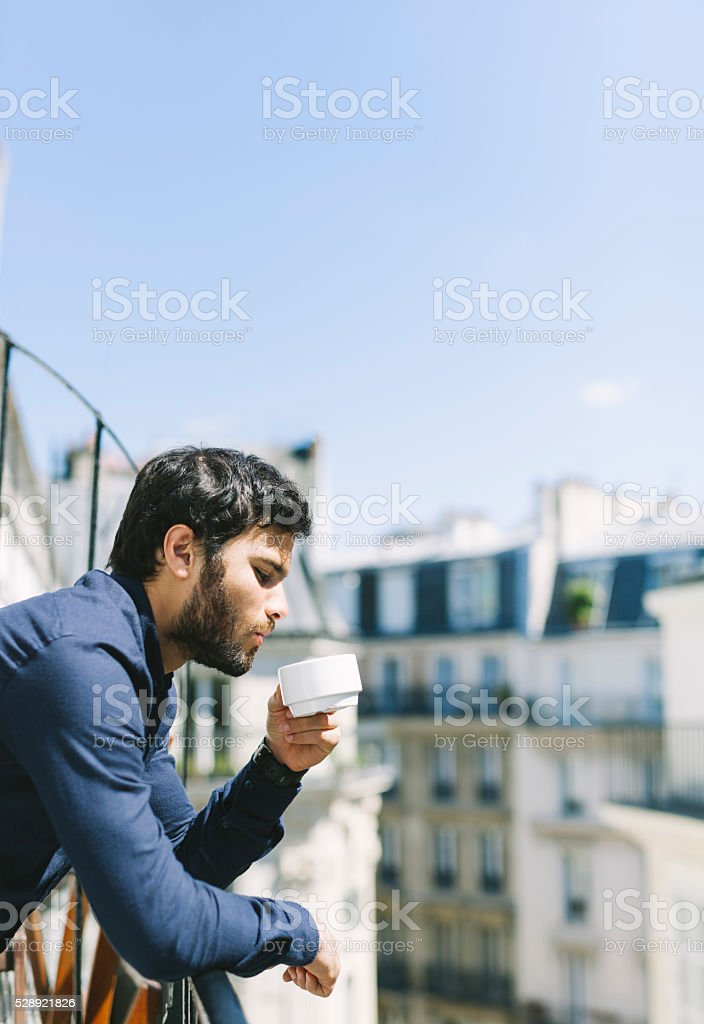 Handsome Young Man Drinking Coffee on a Sunny Balcony stock photo