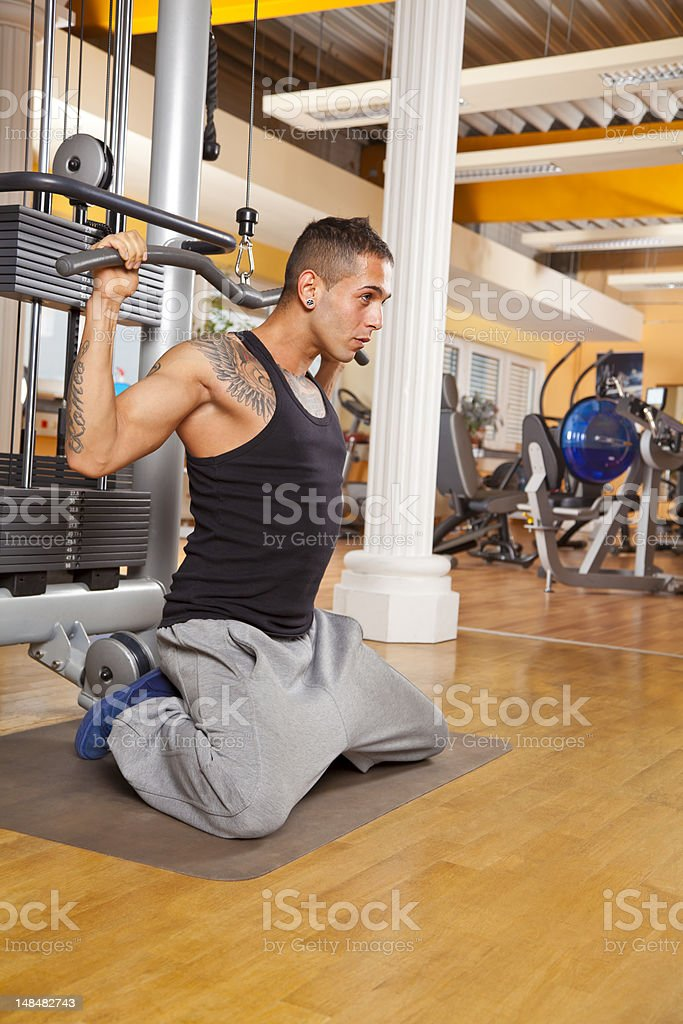 handsome young man exercising in gym training latissimus dorsi stock photo
