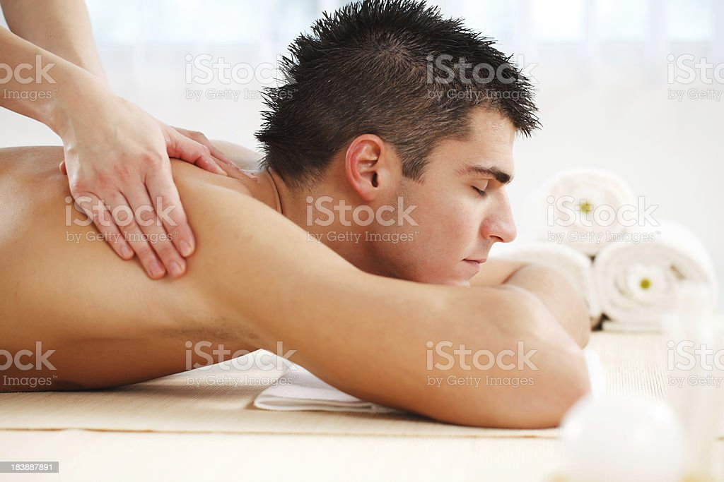 Handsome young man getting a massage at the spa centre. royalty-free stock photo