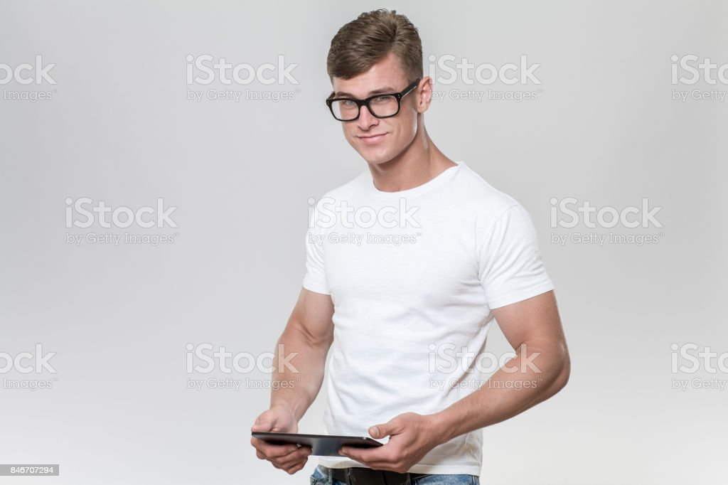 Handsome young man holding a tablet in a studio with grey background. stock photo