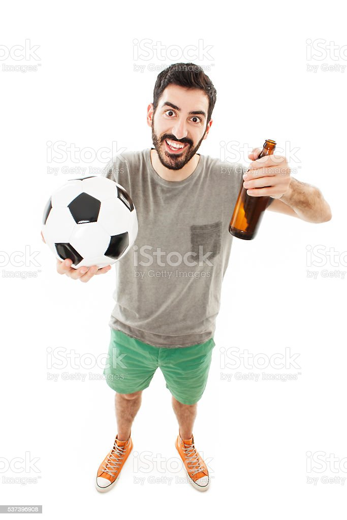 Handsome young man holding ball and beer stock photo