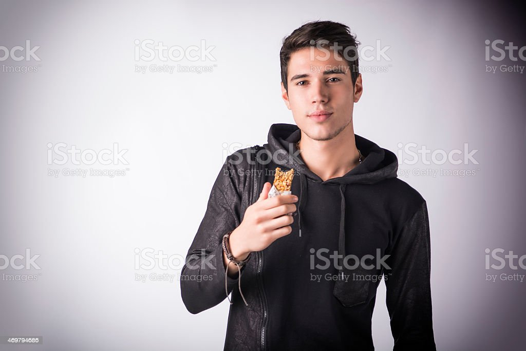 Handsome young man holding the cereal bar he's eating stock photo