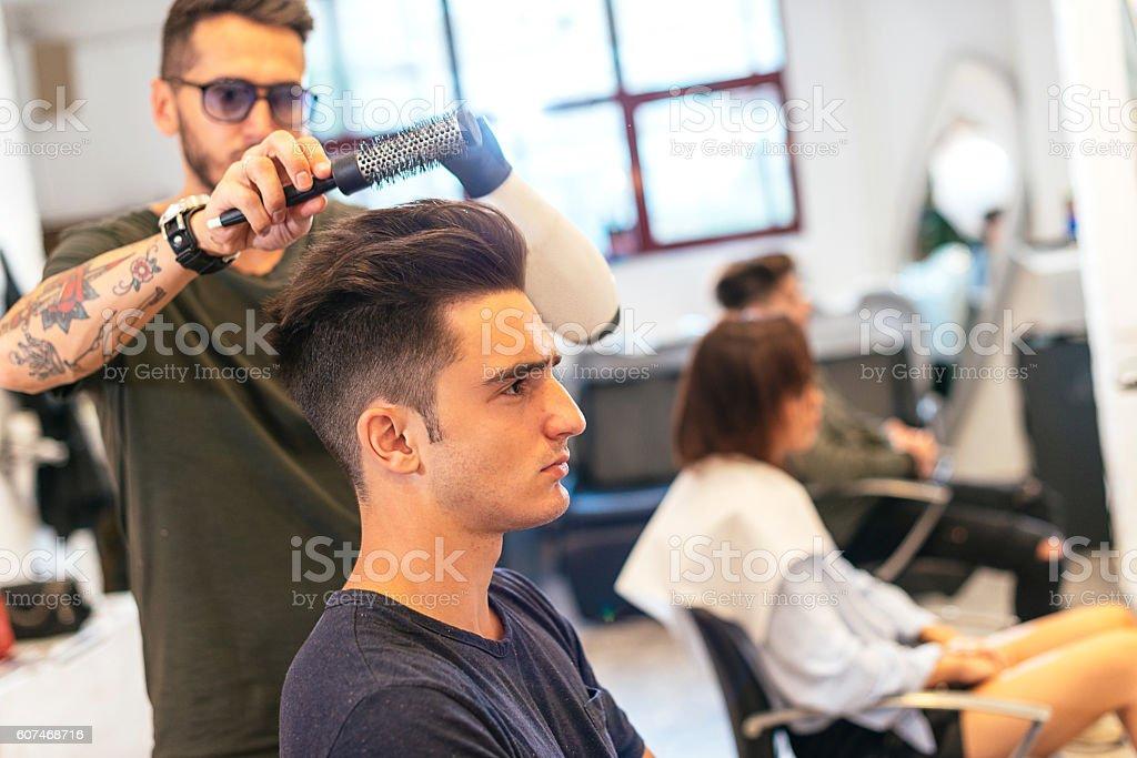 Handsome young man in hair salon having hair cut stock photo