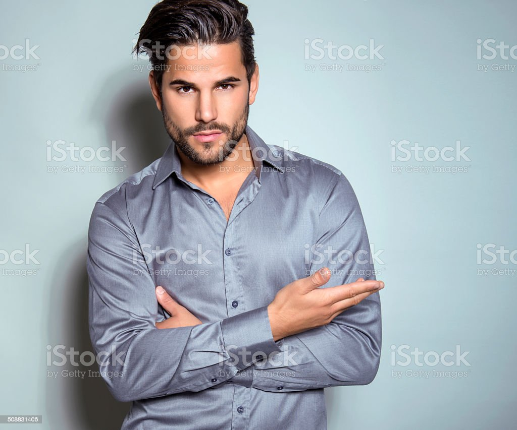 handsome young man in suit on grey background stock photo