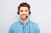 handsome young man in work in  call-centre with headphones