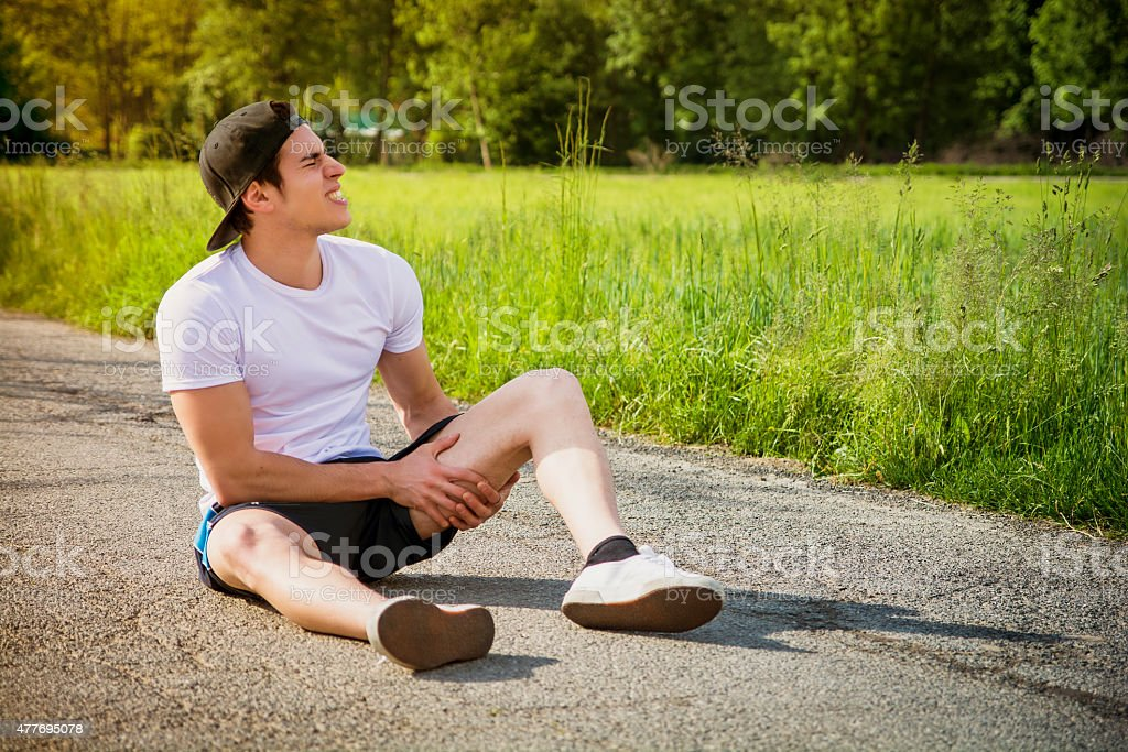 Handsome young man injured while running and jogging on road stock photo