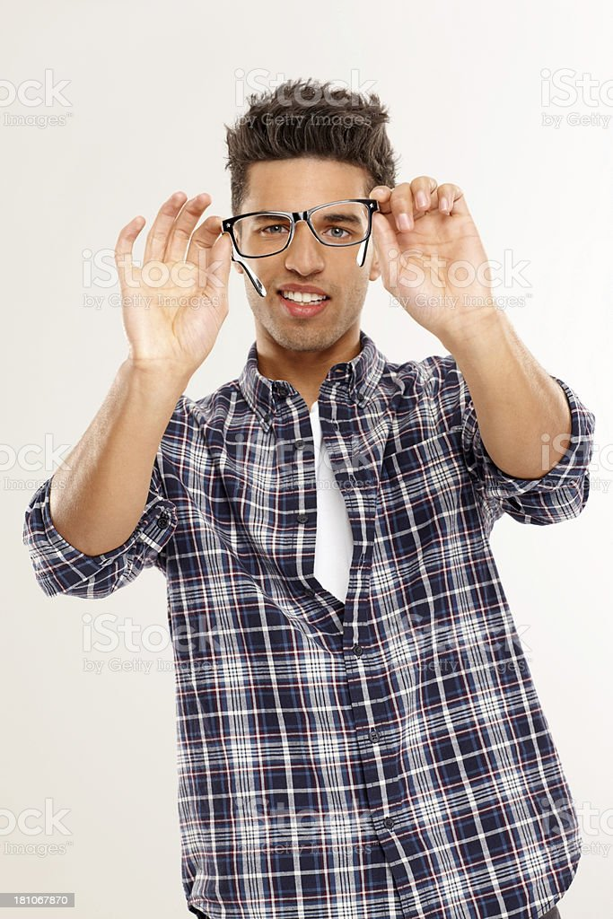 Handsome young man inspecting his spectacles royalty-free stock photo