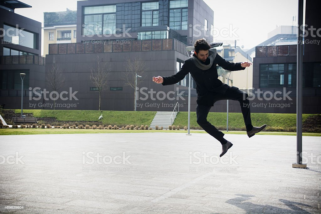 Handsome young man jumping for joy stock photo