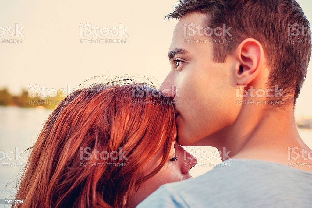 Handsome young man kissing his girlfriend stock photo