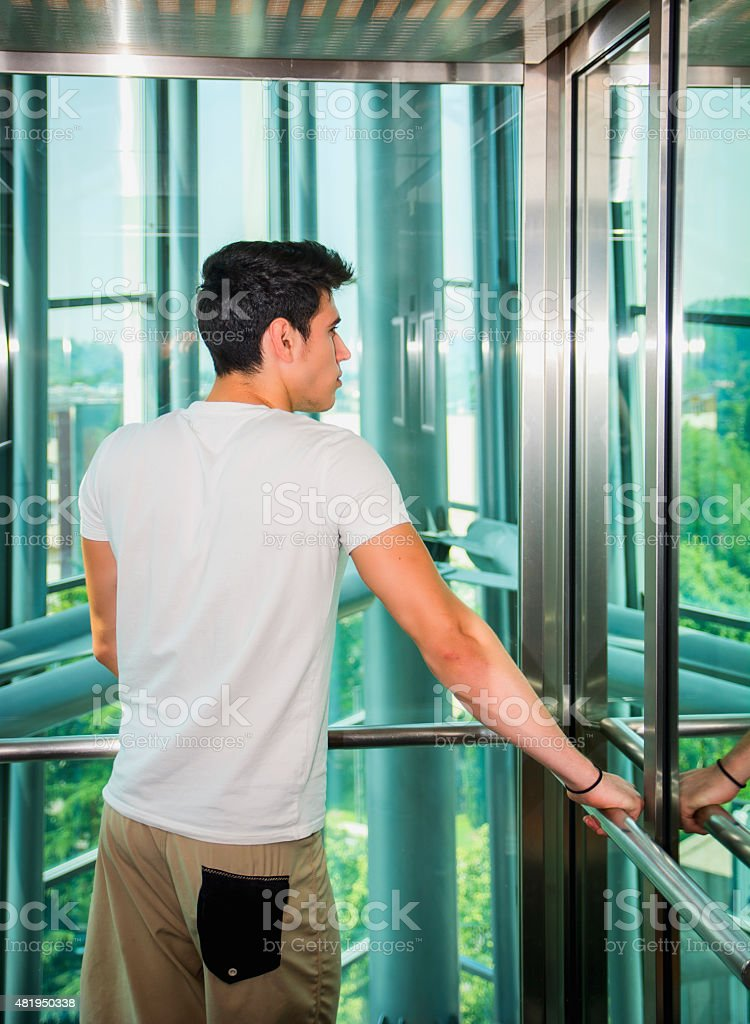 Handsome young man leaning against mirror inside an elevator or stock photo