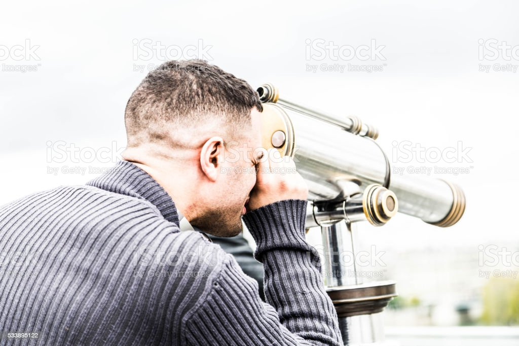 handsome young man looking through telescope at  Paris skyline stock photo