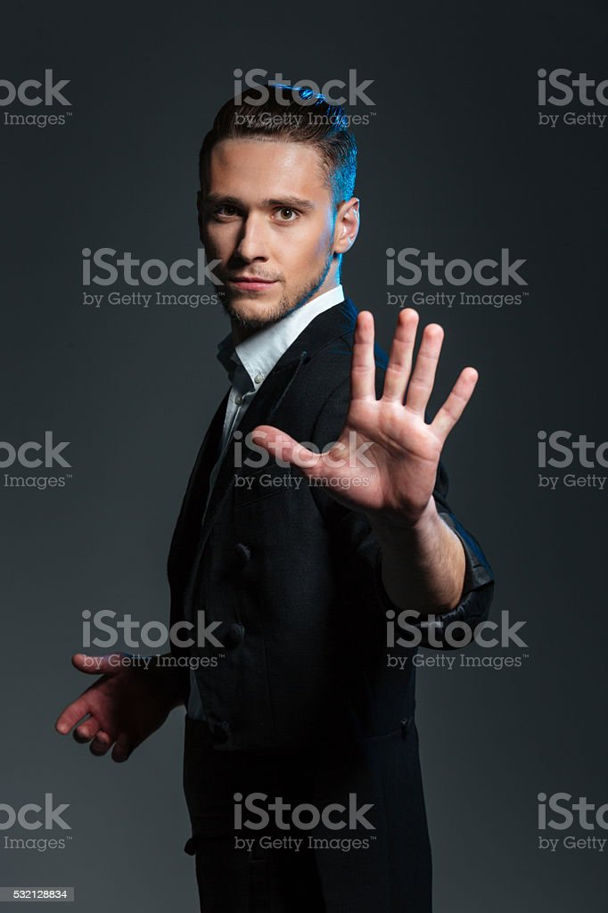 Handsome young man magician showing his palm stock photo