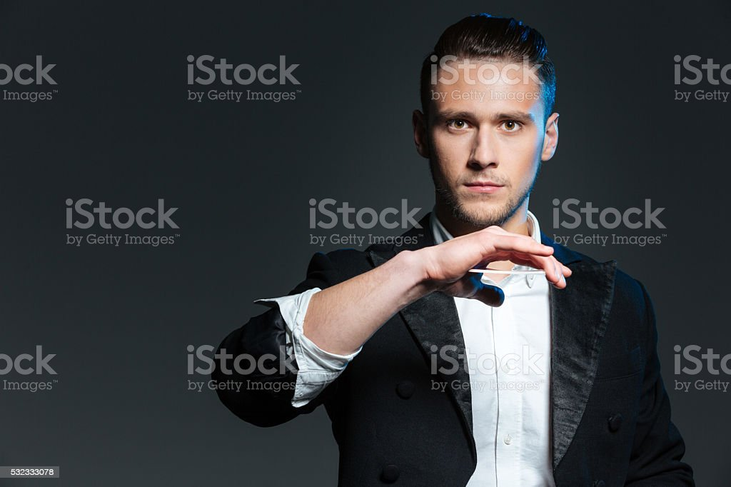 Handsome young man magician showing tricks with playing cards stock photo