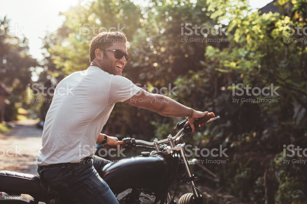 Handsome young man on motorcycle stock photo