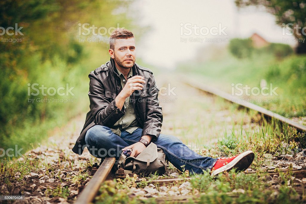 Handsome young man posing outdoors stock photo
