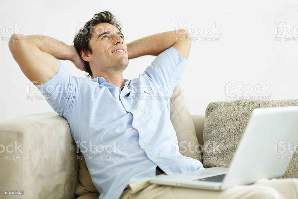 Handsome young man relaxing with hands behind head royalty-free stock photo