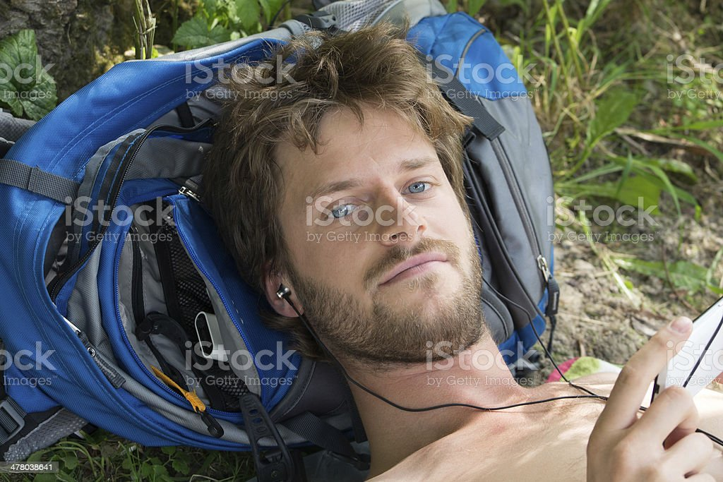 handsome young man resting on his backpack royalty-free stock photo