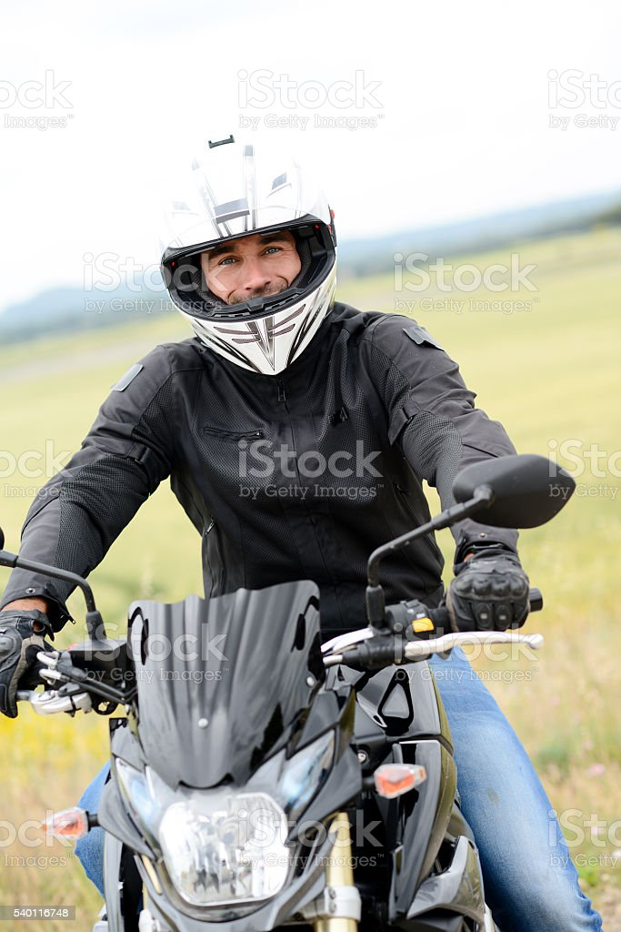 handsome young man riding his black motorcycle stock photo