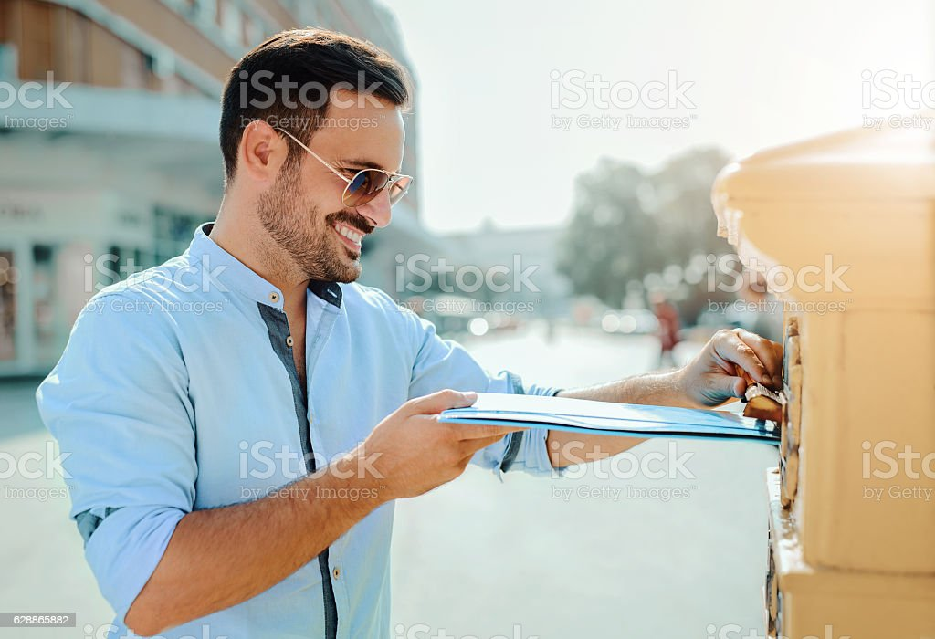 Handsome young man sending a folder and documents via mailbox stock photo