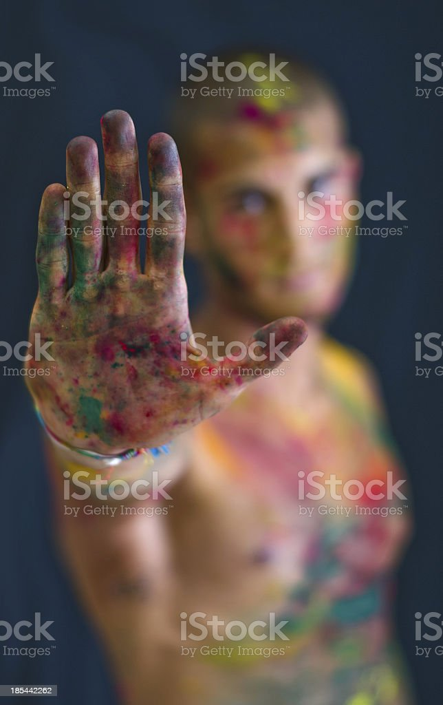 Handsome young man showing hand, skin all painted with colors royalty-free stock photo