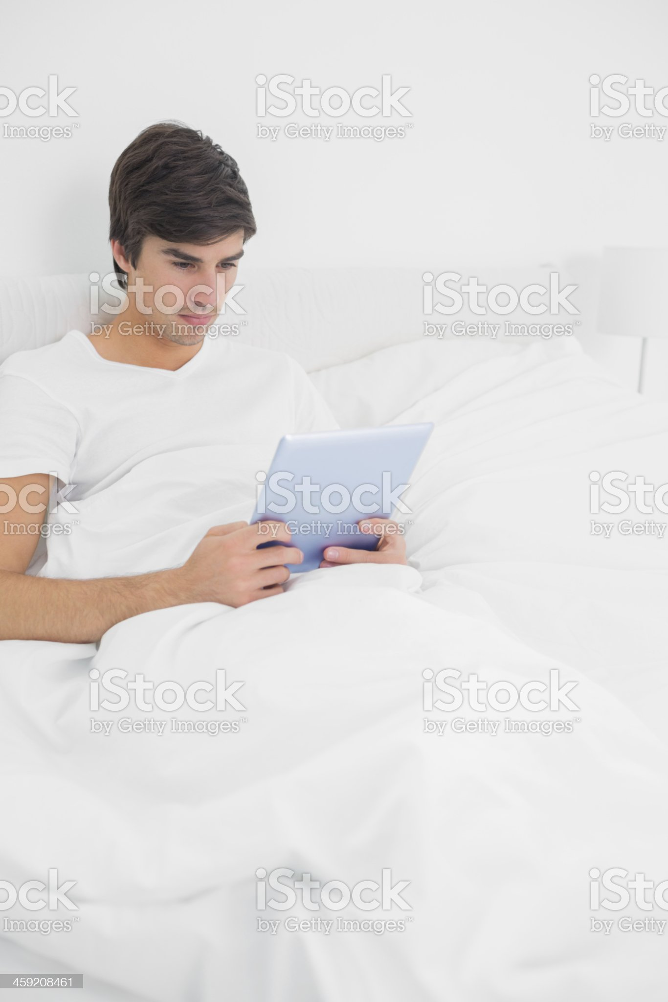 Handsome young man sitting in bed using tablet pc royalty-free stock photo