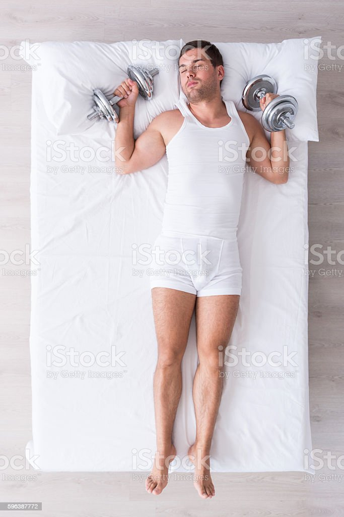Handsome young man sleeping on bed stock photo