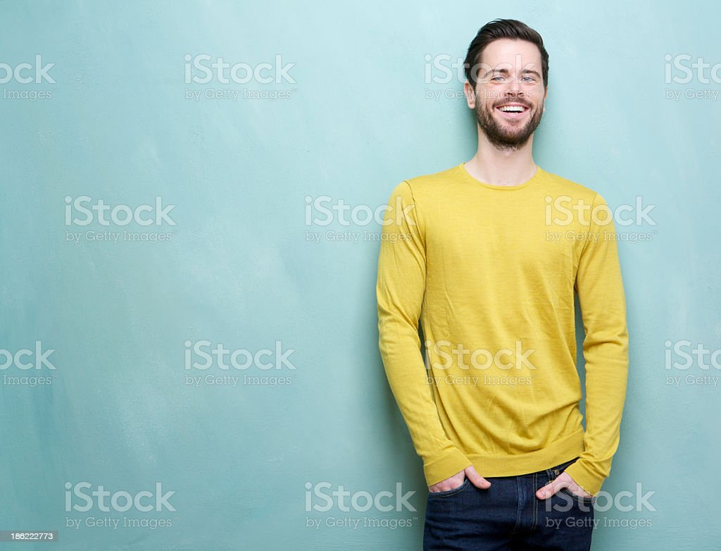 Handsome young man smiling leaning on blue background stock photo