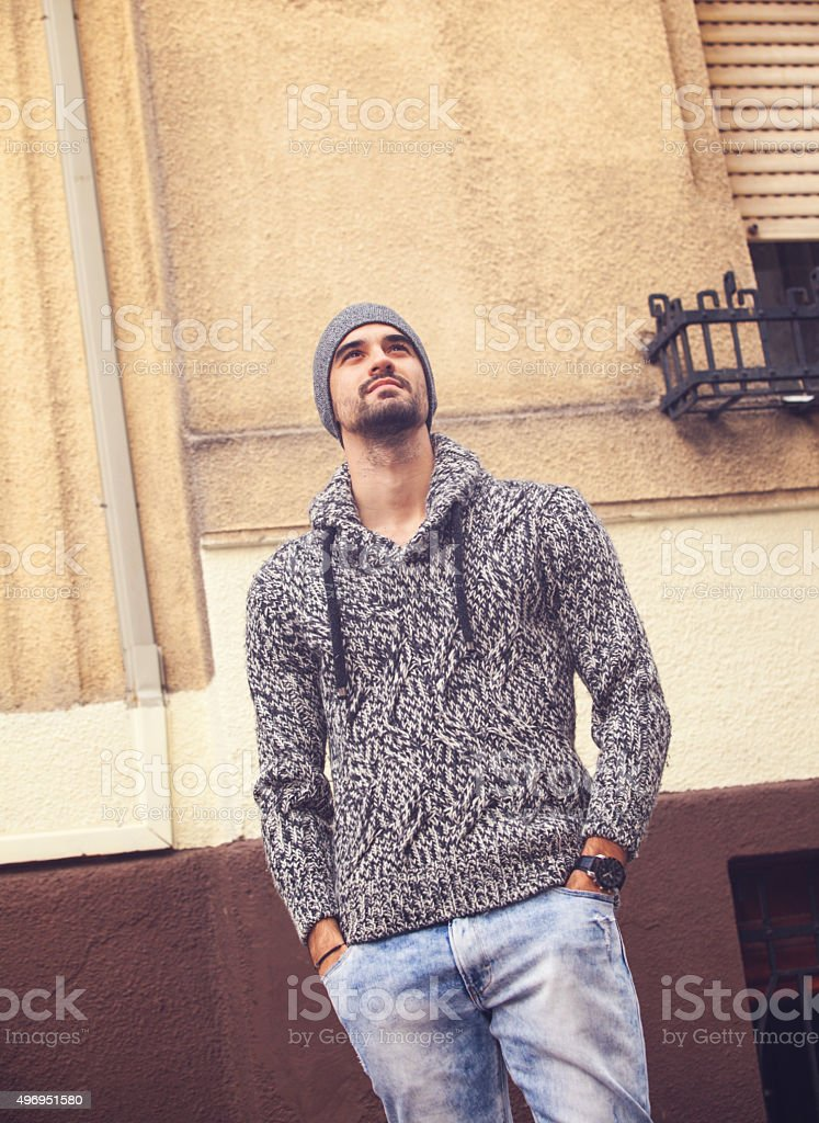 Handsome young man standing by the wall stock photo
