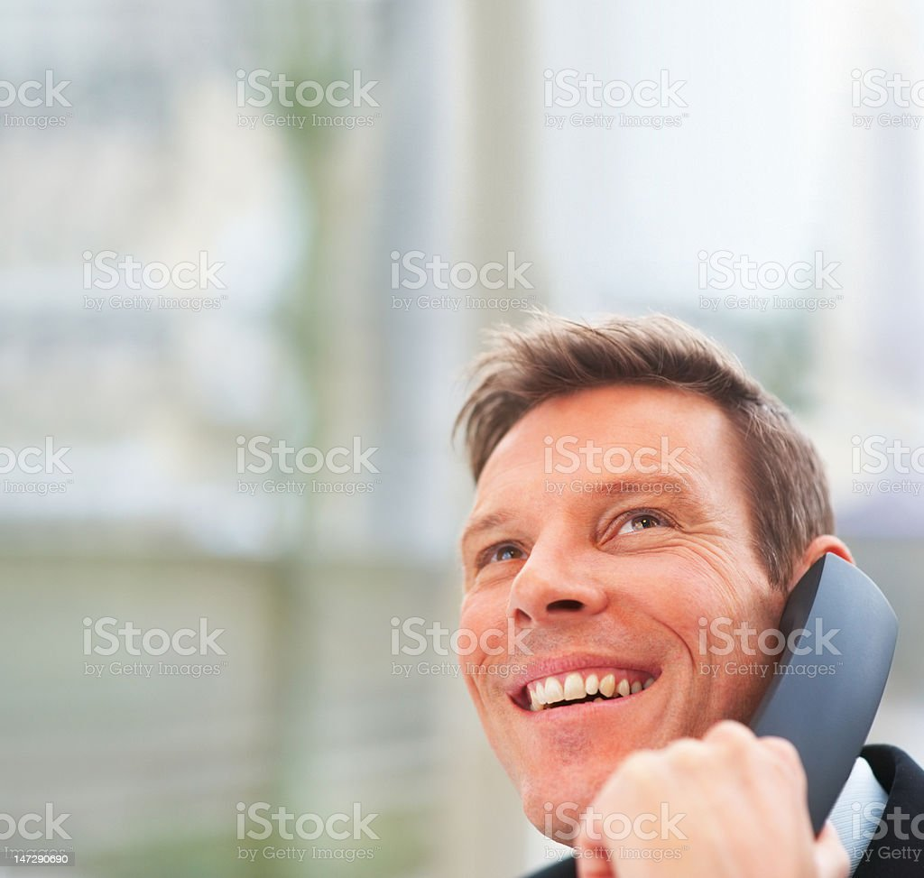 Handsome young man talking on telephone and smiling royalty-free stock photo