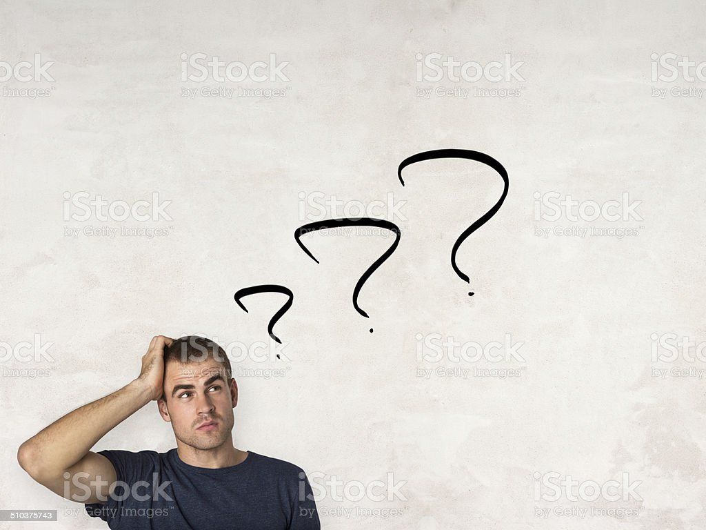 handsome young man thinking and confused stock photo
