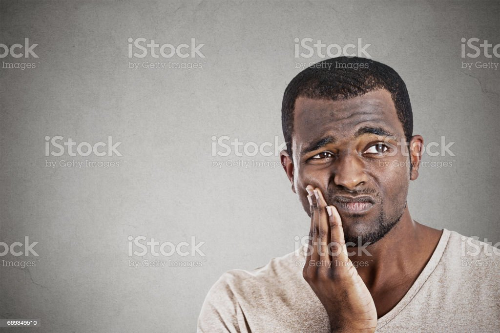 handsome young man touching face having really bad pain tooth ache stock photo