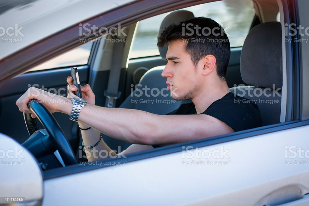 Handsome Young Man Using his Cell Phone Driving a Car stock photo