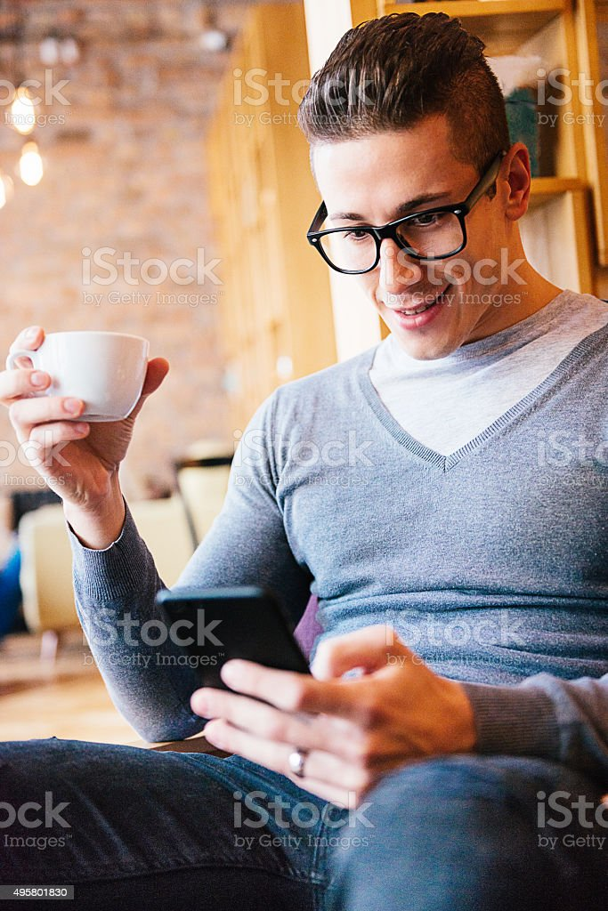 Handsome young man using smartphone for social networking and chat stock photo