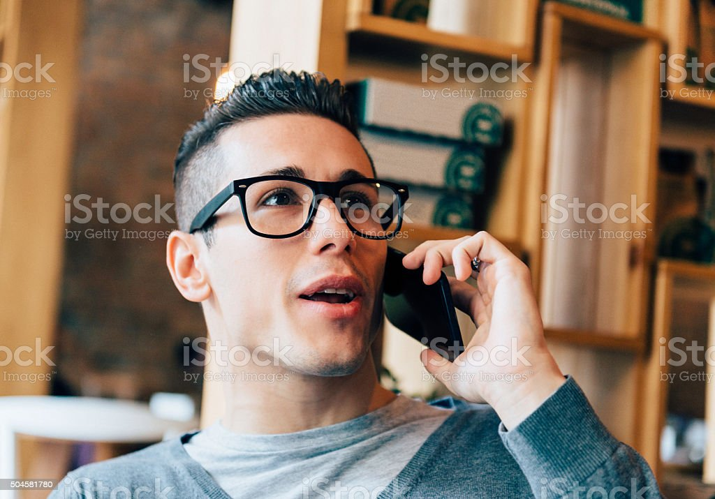 Handsome young man using smartphone for social networking and business stock photo